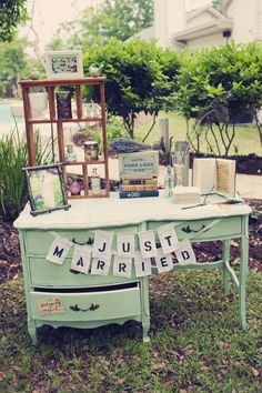 Adorable wedding guest book display on a mint green french provincial desk.