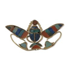 Around 1890 BC. Scarab pendent from Egypt. Reign of Senwosret II, 12th Dynasty. Winged scarab of electrum, inlaid with carnelian, green feldspar, and lapis lazuli. This piece of jewellery is a pendant in the form of a winged scarab. It is made of electrum (a naturally occurring alloy of gold and silver) inlaid with carnelian, green feldspar and lapis lazuli. Two small tubes on the underside of the object were used to suspend it.