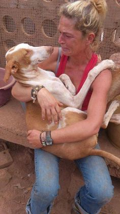 This woman was visiting a Podenco/Galgo/ grey shelter in Spain.... when the dog came to lay on her lap, her heart broke and she decided to adopt him. I Believe it's a beautiful photo that almost needs no words.... Just look what a joy and love you get from one waiting to be saved!