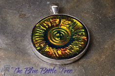 Image of bronze and green circular holographic effect pendant made from polymer clay.