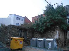 Contenedores junto a construcción típica