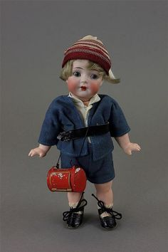 "7 1/2"" K&R SIMON & HALBIG #126 BISQUE SOCKET HEAD CHARACTER ~ GLASS SLEEP EYES, OPEN MOUTH WITH TEETH, MOHAIR WIG, ON 5 PIECE COMPOSITION BODY WITH STARFISH HANDS. COMES DRESSED AS SCHOOL BOY CARRYING ANTIQUE TIN LUNCH BOX."