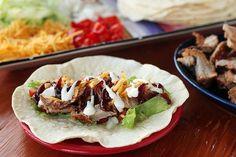 De wraps met varkenshaas worden gevuld met sla, tomaten en uien. Het gerecht wordt verder op smaak gebracht door barbecuesaus, geraspte kaas en kruiden.