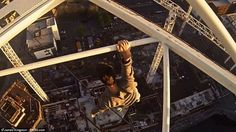 Hold on tight! Mr Kingston dangles one handed from a beam on the 250ft-tall crane