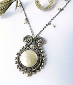 A superb white coin pearl with beautiful lustre is encased in a wire wrapped sterling silver frame. Sterling silver bead and pearl detail with fine sterling chain and 6 tiny pearl dangles. Handcrafted clasp with extender chain. All metal is sterling silver and has been oxidised and polished.