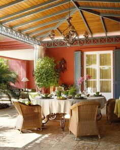 En el porche andaluz, comer a la sombra  Mesa de forja, en Guadarte. Paneras de ratán, cubertería de acero y copas, en Casa y Campo. Tartera de cristal de Teklassic.