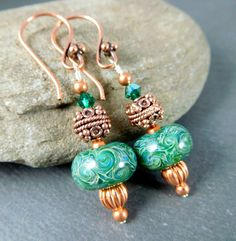 Handmade glass and copper dangle earrings featuring emerald green, blue and cream SRA artisan crafted boro lampwork beads; copper beads; and green Swarovski crystals.  These beautiful earrings are composed of artisan crafted borosilicate glass beads. The boro lampwork beads are green with swirls of cream and hints of blue. Green Swarovski crystals compliment the beads and add sparkle. Copper beads and earring wires complete these stunning earrings.  These earrings are 1.8 inches (4.6cm)…