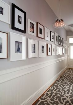 two rows of square frames, in different sizes and colors, containing black and white images, hung on pale gray wall, hallway decor, grey and white floor tiles