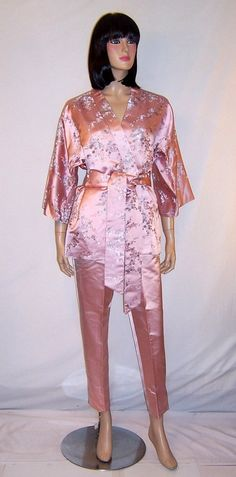 This is a breathtakingly beautiful embroidered silk two-piece lounging ensemble consisting of a finely embroidered jacket with a wide sash and a fitted pair of pink silk cigarette pants with a side zipper made in Hong Kong British Crown Colony and of the 1960s vintage. The ensemble is marked a Size 12, but would be more comparable to a modern day Size 6. It is in excellent, never worn, vintage condition, with the tags still attached.
