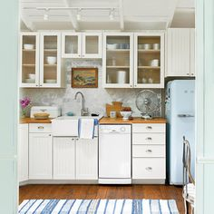 A compact kitchen with neutral cabinets, a vintage refrigerator, and scaled-down appliances
