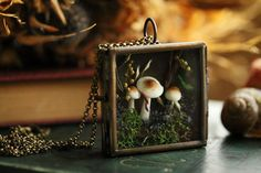 A cluster of tiny brown and white mushrooms peep up among the flowers and wild grasses from the mossy bed of a forest floor. This magical woodland shadowbox locket is handmade with real plants