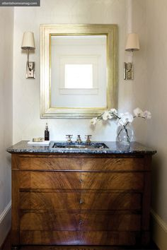 """Howard often converts antique commodes into vanities. In this home's powder room, an antique chest with its original granite top holds a new Waterworks hammered metal sink."" Phoebe Howard"