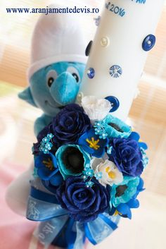 Lumanare de botez cu jucarie strumf decorata cu flori de hartie. Modelul poate fi realizat si cu alte jucarii de plus sau alte culori ale florilor. Baptism Candle, Candles, Babies Clothes, Flowers, Handmade, Crafts, Party Ideas, Events, Weddings