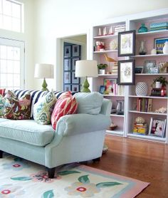 Colorful and bright.  Patterned cushions. I like the pictures hanging on the bookshelves.