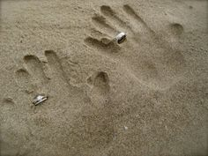 """a rings/honeymoon photo: the bride and groom's hand prints in the sand, """"wearing"""" the wedding rings"""