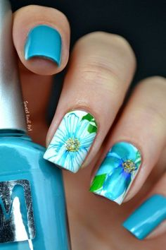 Blue floral nail art design. This pretty little nail art design sports a blue and white base colors with a lighter blue polish on top for the flower details and green polish for the leaves.