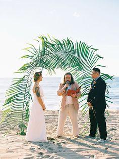 Beach wedding altar idea with large palm tree leaves