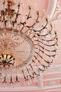 Pink ceiling with white moulding and an extra large, beautiful chandelier