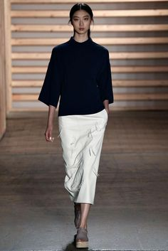 Tibi Spring 2015: A white leather pencil skirt with fringe detail and a black cotton sculpted top worn with grey, peep toe flatform shoes.