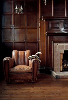 Beautifully worn leather club chair + timber paneling + classic fireplace = perfect retreat