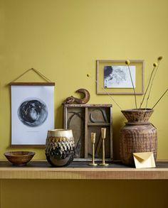 Gele wand met houten en gouden accessoires | yellow wall with wooden and gold…