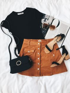 Black basic tee with velvet tan button up a line skirt with black strappy block heels and black satchel handbag. Summer outfit inspo.