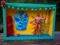 This is a handmade Luchador art box that is primarily mint green and bright yellow in color. It features a vintage Mexican Wrestler action figure,