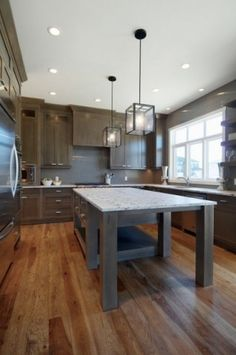 Dark grey cabinets. cool lights. Wide floors. - love the gigantor island/counter height table