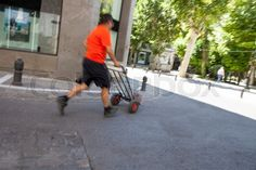 Stock image of 'Mature running delivery man carrying a hand truck on city center…