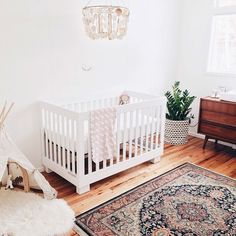 nursery - wood floors, white walls and crib, chandelier, persian rug, and mid century furniture
