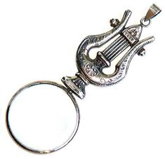 A late 19th century antique magnifying glass in a sterling-marked silver lyre-shaped mount (four inches long) for a chatelaine. [Alex Peck Antique Scientifica-Catalogue, P. 15]