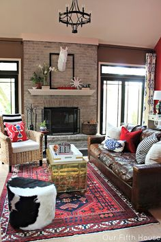 whitewashed brick fireplace with dark furniture and pops of bold colors.