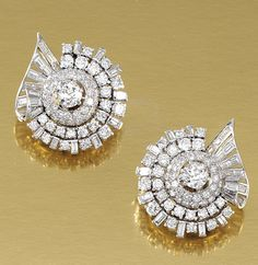 PAIR OF DIAMOND EAR CLIPS, 1950S. Each clip of geometric design embellished with circular-cut and baguette diamonds, clip fittings, French import marks.