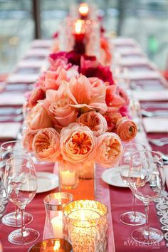 wedding reception decor: blush, pink and magenta garden roses, orchids, ranunculus on long table setting.