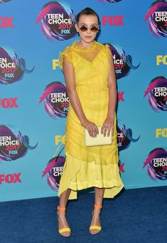 Millie went down the romantic route at the Teen Choice Awards with a yellow Kenzo dress. She accessorized i...