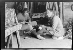 Edgar Williams, right, and another man [Tracy Thomas Gough?], who is preparing food, sitting in front of a fireplace in a mountain hut, Southern Alps, Canterbury Region 1917