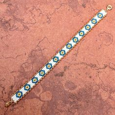 I have hand-stitched this cute, petite bracelet with glass Delica seed beads in a soothing combination of colors ~ ivory, teal, buttercup and gold. It is perfect to wear with so many of your favorite outfits, from blue jeans to suits! Dont let the delicate look of this bracelet