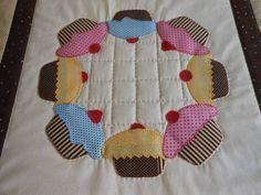 Trilho de mesa com motivos de cupcakes.Tecido 100 % algodão e manta acrílica internamente.Mede 55 cm de largura x 112 cm de comprimento. R$ 80,00