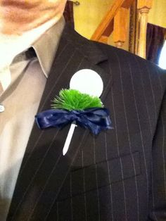 A golf ball, on a tee, with bright green grass and a pretty bow!  Super simple, and super cute.