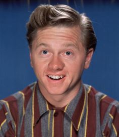 Promotional headshot portrait of American actor Mickey Rooney smiling broadly in front of a blue backdrop 1940s He wears a striped flannel shirt
