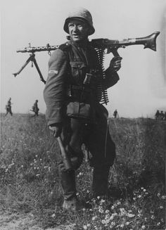 German soldier armed with an MG-34 machine gun and grenade in a field near Oryol.