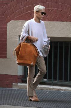 Zoe Kravitz rides the subway in style. Tan tote, khakis and white.