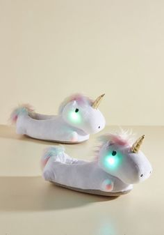 Illuminate your path - and maybe even your heart - by snuggling your feet into these light-up slippers! Fashioned into twin unicorns that glow from within in response to your movements, these battery-powered beauties satisfy your want for whimsy in a most 'de-light-ful' way!