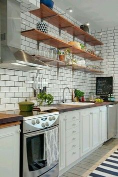 Farmhouse kitchen decor. White subway tile with dark grey grout, no upper cabinets, white lower, butcher block counter, open shelves, stainless hood #ad #fixerupper #farmhousekitchen #nouppers #butcherblock #subwaytile