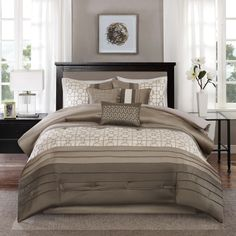 The top of bed features a dark taupe and tan pieced together with a strip of ivory with geometric embroidery. Three decorative pillows use the fabrics and designs from the top of bed to complete this cohesive look.