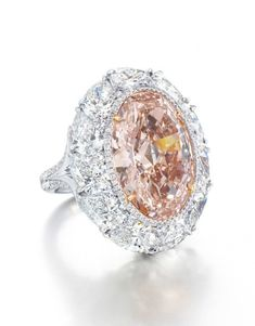 A RARE COLOURED DIAMOND AND DIAMOND RING Centering upon an oval-shaped fancy intense orangy pink diamond weighing approximately 12.85 carats, within a brilliant-cut diamond border and pear-shaped diamond surround, joined to the brilliant-cut diamond bifurcated half-hoop, mounted in platinum and 18k rose gold