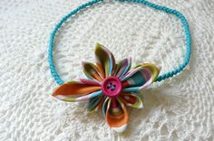 Citrus coloured pointed kanzashi flower on a turquoise braided skinny elastic headband made by ImwtheBand