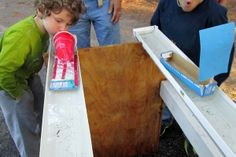 Two boys blow on the sales of their homemade model boats, which are floating in