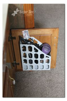 Tack a magazine holder to the inside or you cabinet as the perfect hair dryer holder!