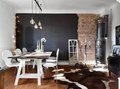 girlanda z żarówkami,stojący kuty świecznik, żarówki na kablu,czarna ściana połączona z czerwoną cegłą,dywan łaciaty z bydlęcej skóry,biały stół z drewnianym blatem i czarny ceramiczny piec w jadalni